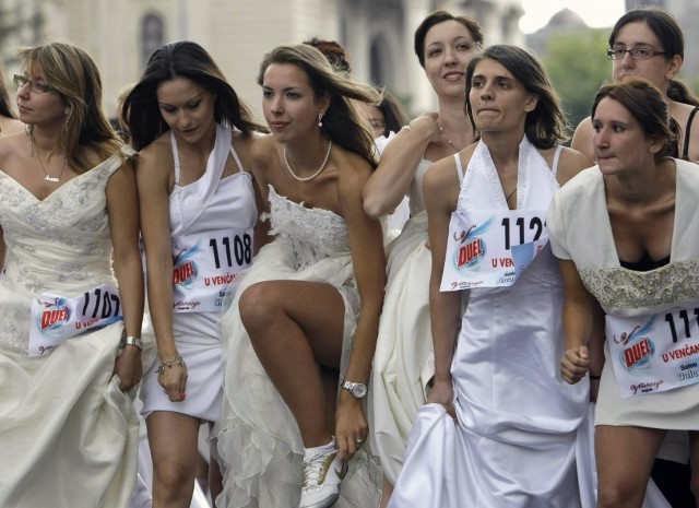 brides with wedding dresses and sneakers, getting ready for the run