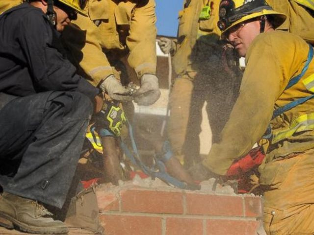 firefighters taking out the bricks of the chimney to get the stuck woman out