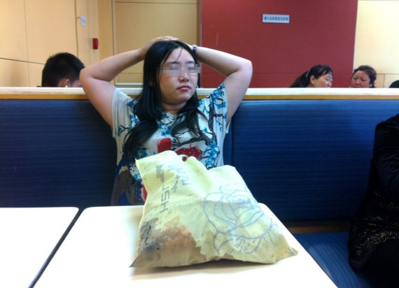 Tan shen sitting in a KFC at a train station