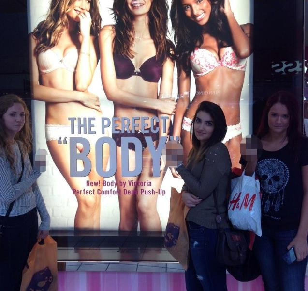 Frances Black, Gabriella Kountourides, and Laura Ferris standing in front of one of the posters of Victoria's Secret's the perfect 'body' campaign