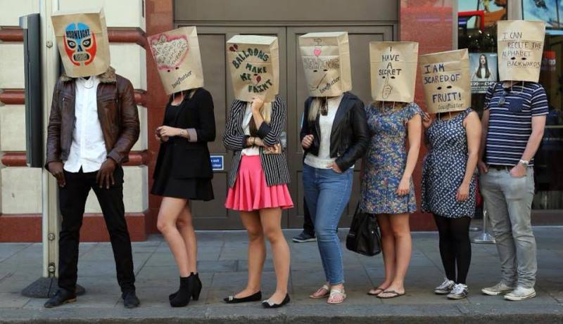 participants wearing paper bags, ready for the speed dating event