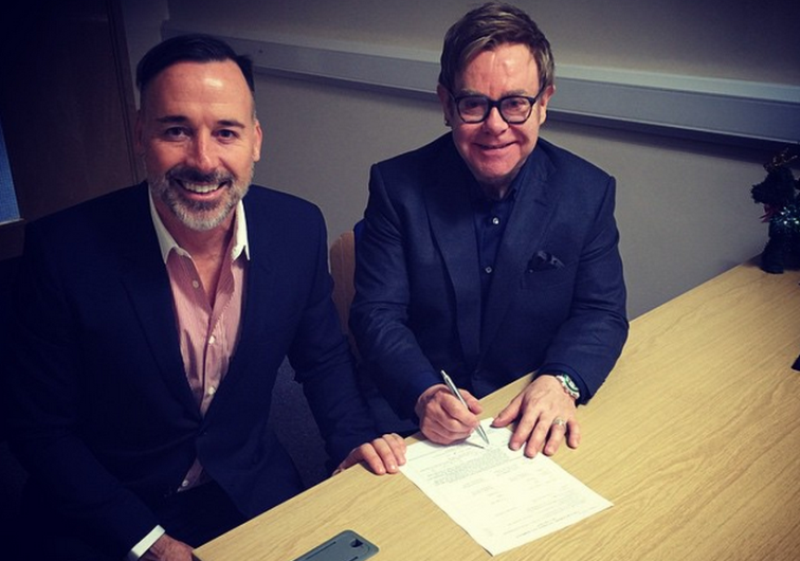 david furnish and sir elton john signing the official documents of their marriage ceremony