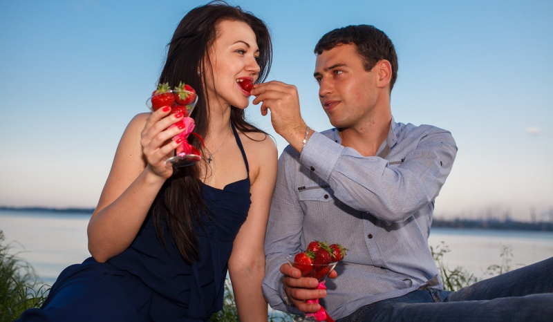 man feeding strawberries to woman