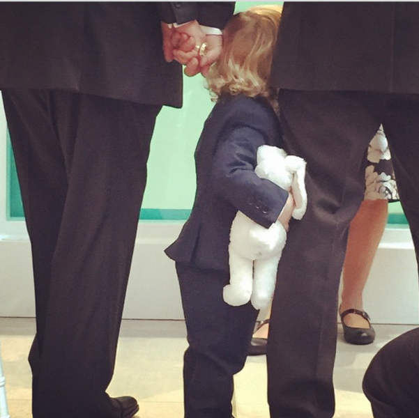 the couple's younger son, elijah, holding on to his father's leg, whilst holding a stuffed toy
