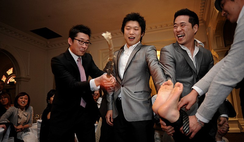 bride's male relatives beating the groom's feet in korea