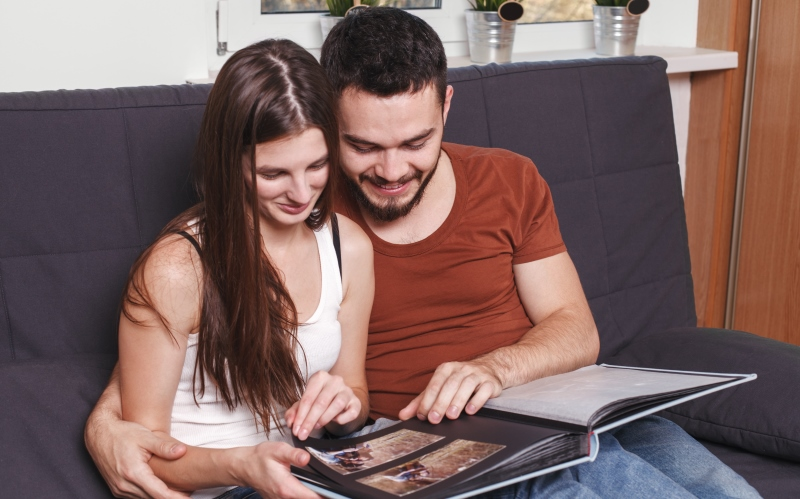 couple looking at an album together_New_Love_Times