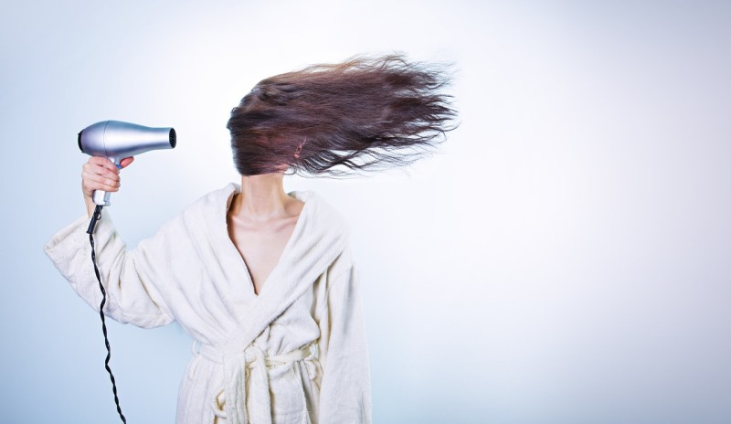 woman blow drying hair