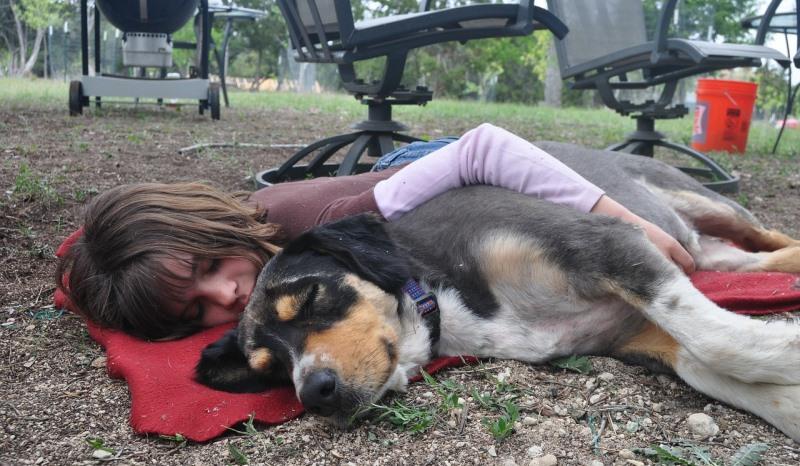 girl cuddling a dog