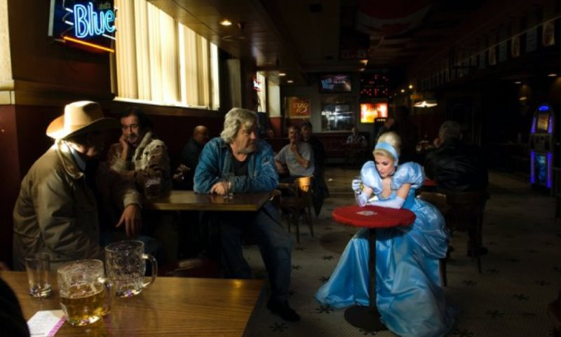 cinderella shown in a dingy bar, contemplating her shot glass