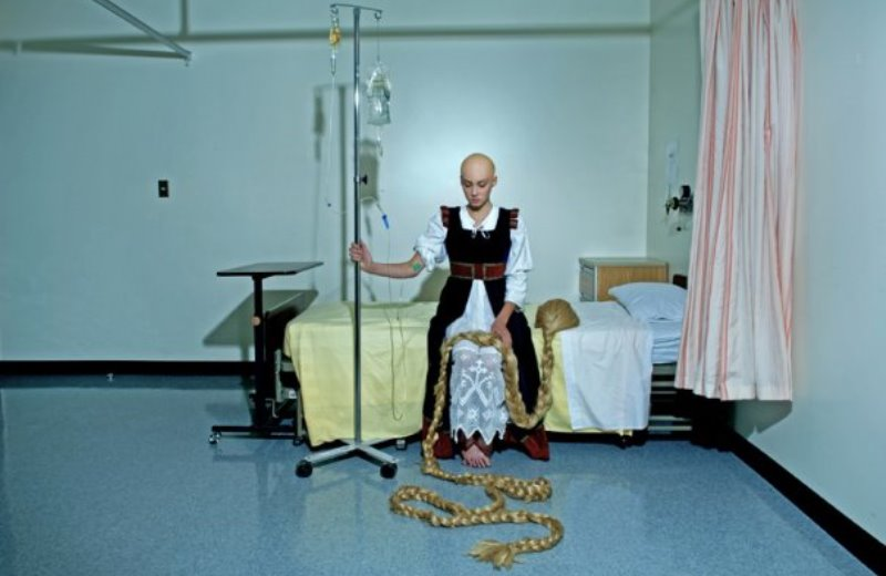 rapunzel sitting forlornly on a hospital bed, clutching her wig, which she lost to chemo