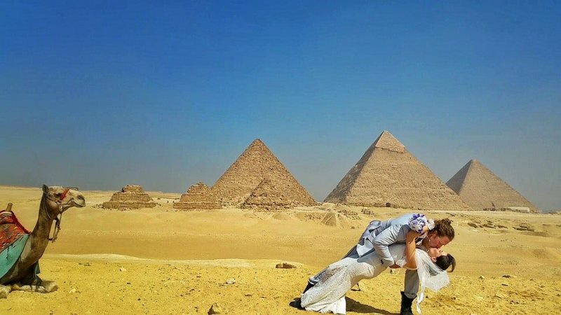 the couple kissing in front of the pyramids of giza