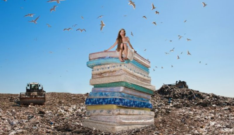 the princess from the princess and the pea sitting on a stack of mattresses in a landfill
