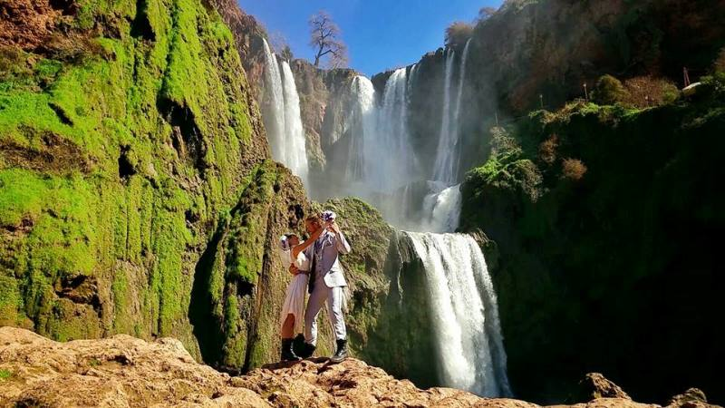 their wedding in front of the ouzoud falls outside marrakesh, morocco
