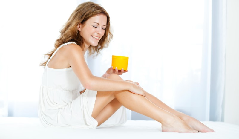 woman applying moisturizer to her legs