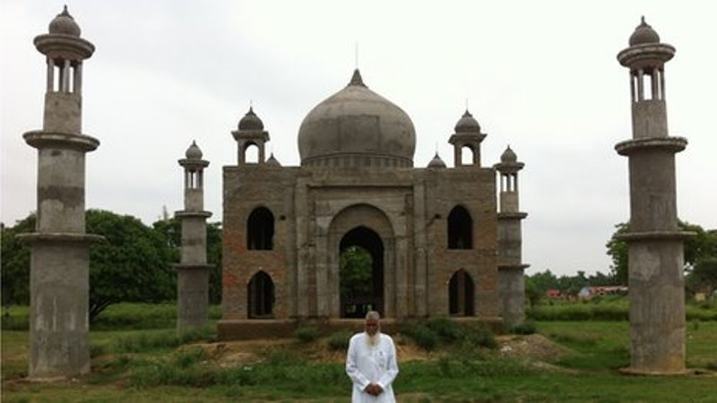 faizul hasan qadri standing in front of the replica of taj mahal that he's building for his late wife