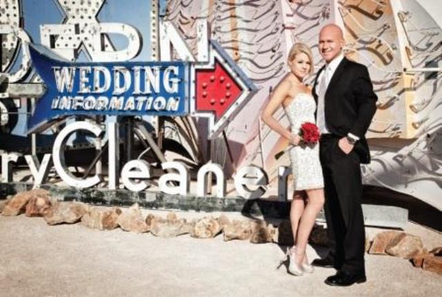 a newlywed couple standing in front of the neon museum