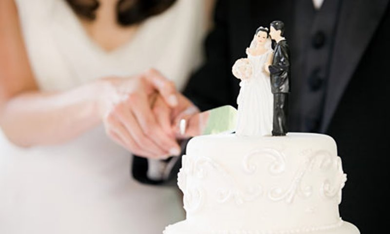 couple cutting wedding cake_New_Love_Times