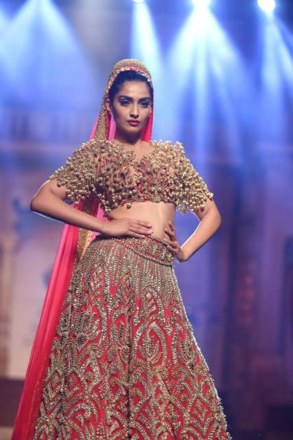 Sonam Kapoor looking stunning in a red and gold ghagra by Abu Jani Sandeep Khosla