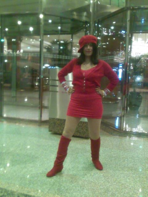 radhe maa in a short red dress and knee-high boots