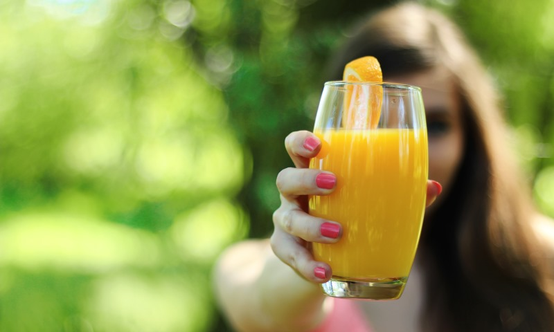 woman holding a glass of juice_New_Love_Times